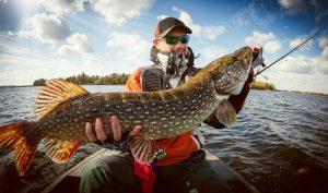big sky montana fishing, guy catching fish on a boat