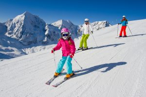 Young family skiing down a snowy slope