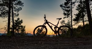 Mountain bike sunset silhouette on forest trail, inspiring landscape. Cycling bike on rural country road. Full suspension bicycle, inspirational sports concept outdoors.