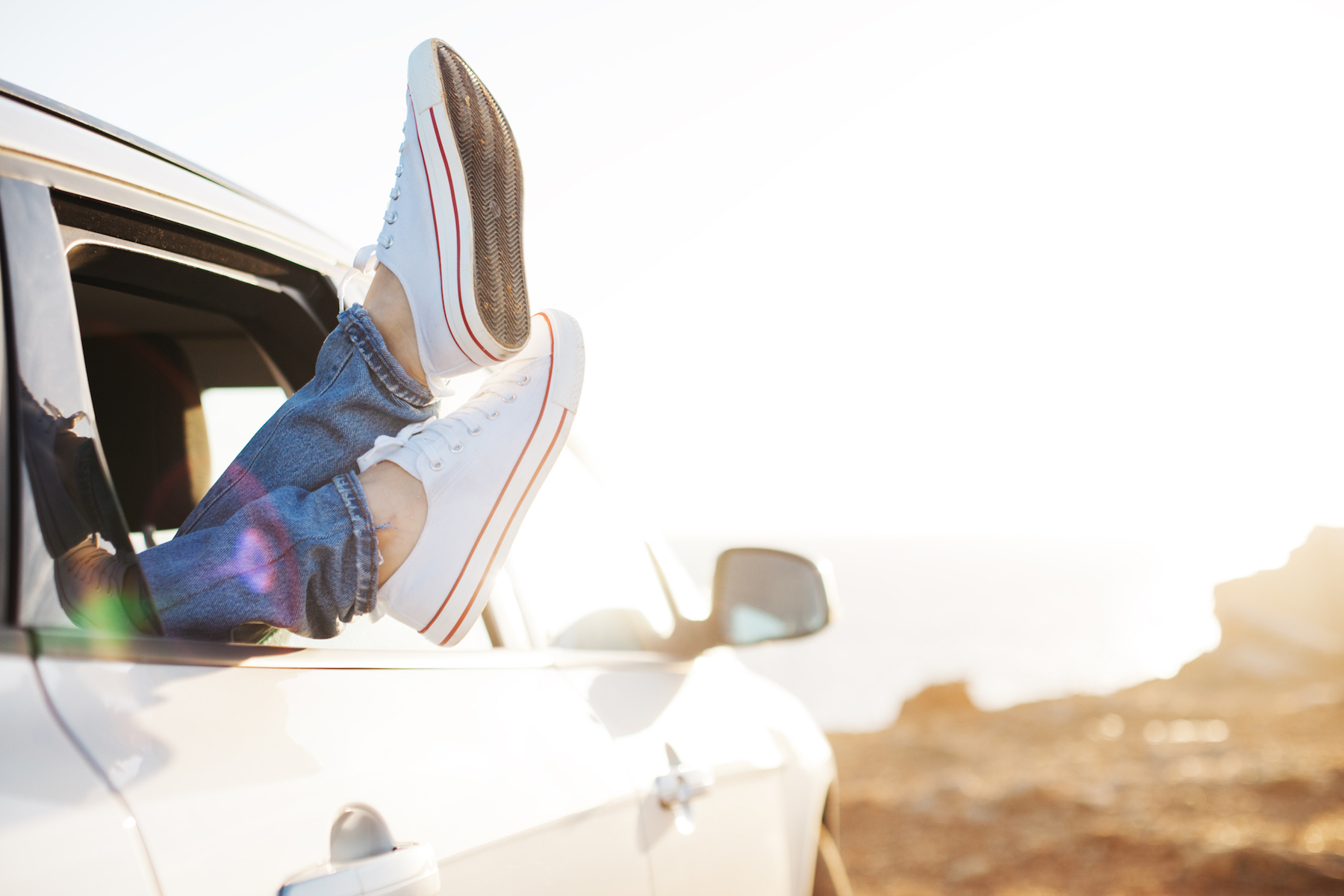 Traveling woman resting in the car with sneakers out of the window